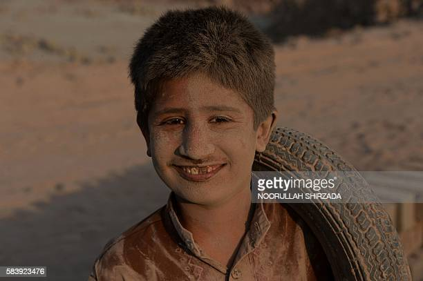 In this photograph taken on July 27 an Afghan boy poses for a photograph along a dusty road on the outskirts of Jalalabad. / AFP / NOORULLAH SHIRZADA