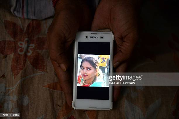 In this photograph taken on July 28 34 year old Indian man Santosh Singh shows a photograph of his wife Supriya Singh on his mobile phone at his...