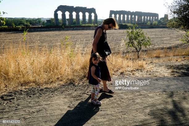 In this photograph taken on July 28 a woman and child walk near the ruins of an ancient Roman aqueduct in a park in a suburb of Rome Two years of...