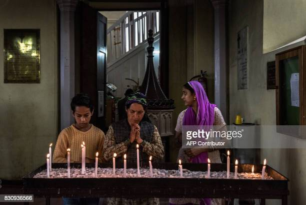 In this photograph taken on July 30 Indian Christian worshippers light candles at the end of Sunday mass at Christ Church in Shimla Kolkata evolved...