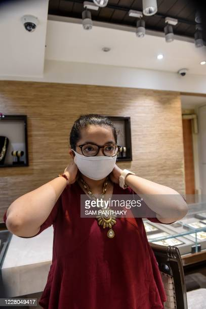 In this photograph taken on July 31 a customer wearing a facemask as a preventive measure against the COVID19 coronavirus tries a necklace made of...