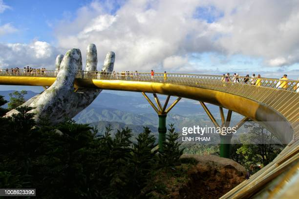 TOPSHOT In this photograph taken on July 31 visitors walk along the 150meter long Cau Vang 'Golden Bridge' in the Ba Na Hills near Danang Nestled in...