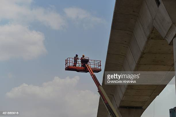 In this photograph taken on July 4 Indian labourers work at a construction site in New Delhi India's new government is due to present its first full...