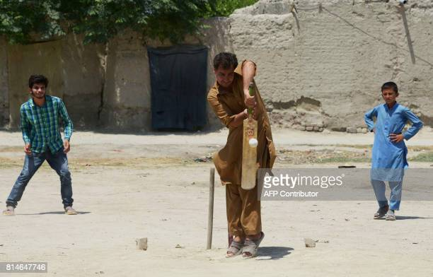 In this photograph taken on July 6 Afghan refugees play a cricket match at the Khurasan refugee camp in the suburbs of Peshawar In dusty Pakistani...