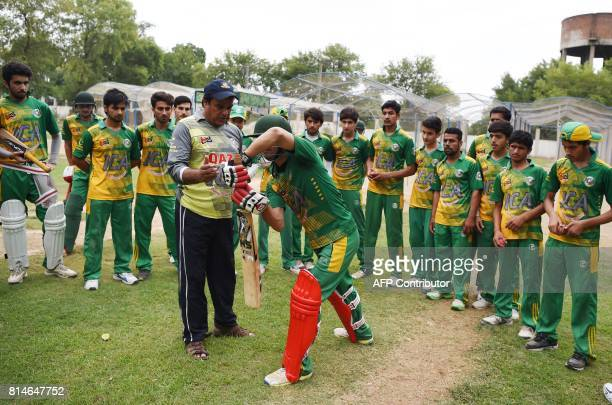 In this photograph taken on July 6 Qazi Shafiq a senior Pakistani cricket coach who coached players on the Afghan national cricket team gives batting...