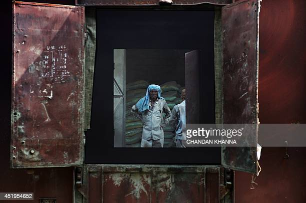 In this photograph taken on July 7 an Indian laborer looks on as he unloads cement bags from freight trains at the Shakur Basti station in New...