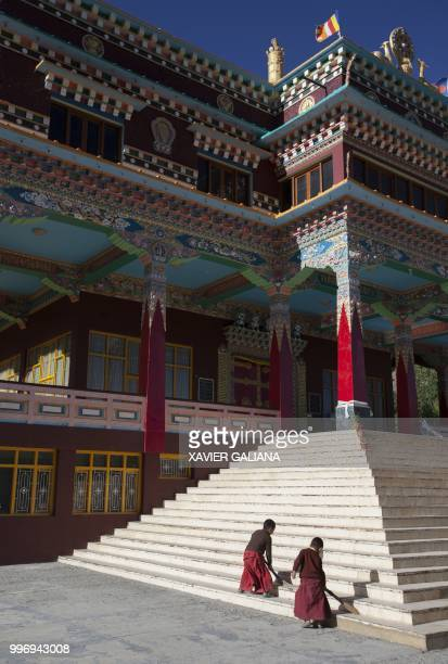 In this photograph taken on July 7 young Indian Buddhist monks sweep the steps of the Sakya Gompa in the town of Kaza in Spiti Valley in the northern...