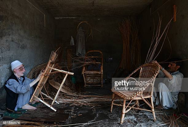 In this photograph taken on July 8 Kashmiri craftsmen make wicker chairs at a workshop on the outskirts of Srinagar India's new government is due to...