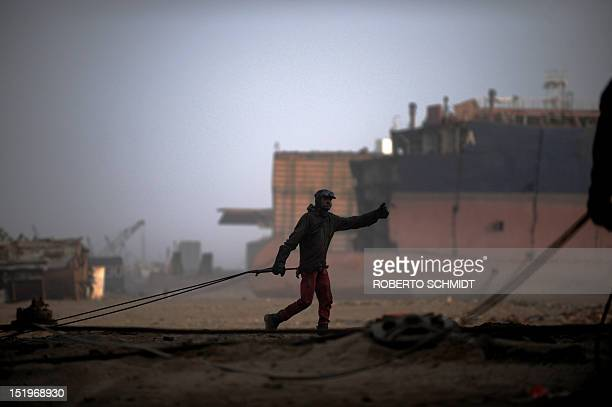 In this photograph taken on July 9 a Pakistani shipyard worker carries a blow torch as he heads to to cut up metal from a vessel beached at one of...