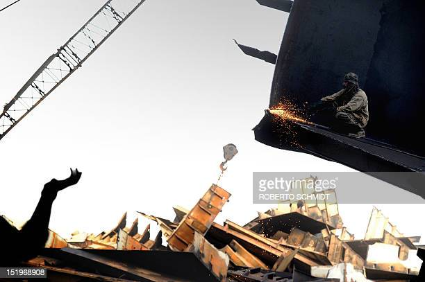 In this photograph taken on July 9 a Pakistani shipyard worker uses a blow torch to cut through a metal platform of a vessel beached and being...