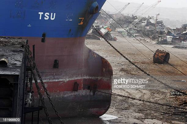 In this photograph taken on July 9 a shipyard worker climbs down from the metal carcass of a ship at the end of his shift in one of the 127...