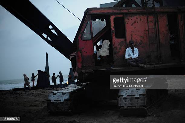 In this photograph taken on July 9 crane spotter Farhan sits on a crane as he waits for a large piece of metal to be moved on the yard in one of the...