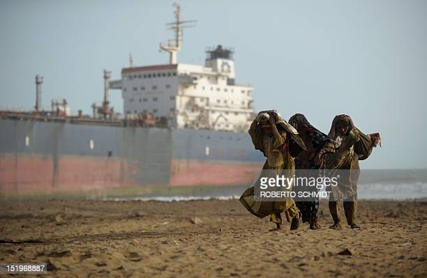 In this photograph taken on July 9 Pakistani workers carry sacks filled with scrap metal pieces they picked up on the shore near where vessel have...