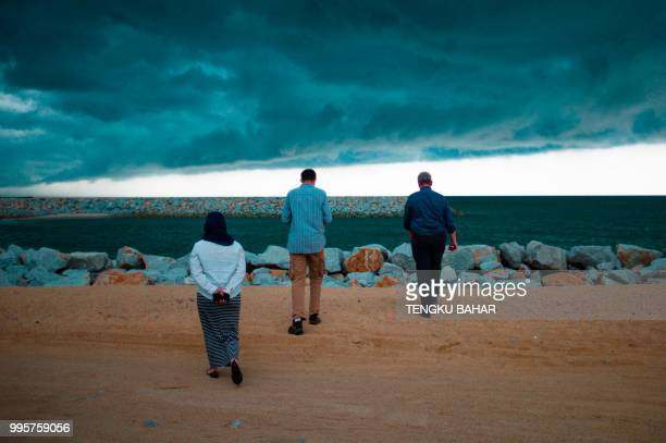 In this photograph taken on July 9 people walk towards a breakwater by the beach as an incoming storm front moves in from the coast near Kuala...