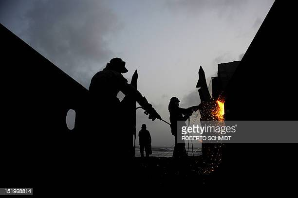 In this photograph taken on July 9 shipyard workers blow torches to cut through metal coming off the hull of a ship being dismantled in one of the...