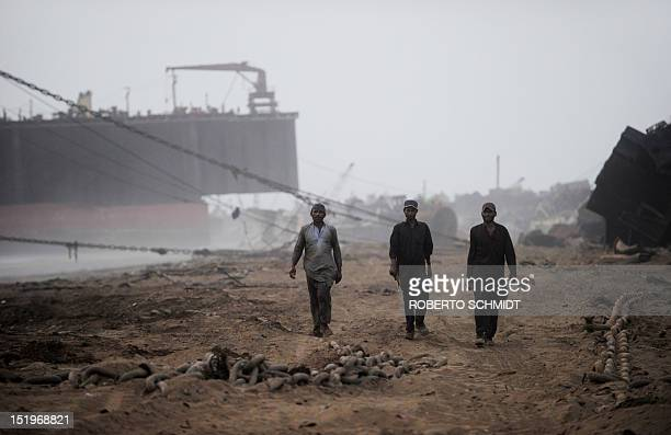 In this photograph taken on July 9 shipyard workers walk away from ships being dismantled and towards the shacks they call home at the end of their...