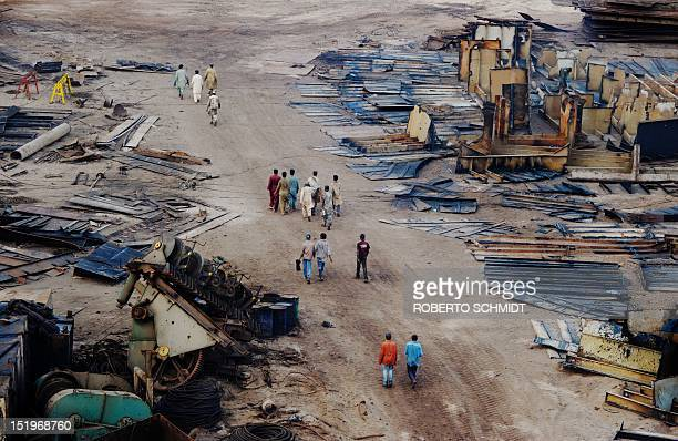 In this photograph taken on July 9 shipyard workers walk past cut metal pieces and other remnants of a dismantled ship laid out on the yard in one of...