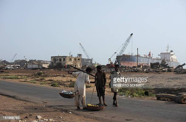 In this photograph taken on July 9 two shipyard wokers buy fruit from a street salesman near one of the 127 shipbreaking plots in Geddani some 40Kms...