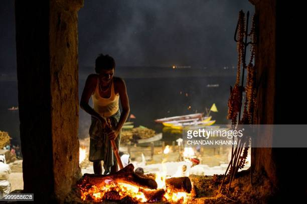 "In this photograph taken on June 1, 2018 an Indian man tends a ""sacred fire"" that is maintained by members of the Dom community and given to Doms to..."
