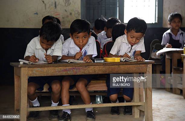 In this photograph taken on June 1 Indian schoolchildren and teachers take part in lessons in classrooms at Rashtriya Swayamsevak Sanghrun Sankardev...