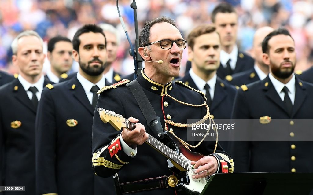 In this photograph taken on June 13, 2017, Jean-Michel Mekil (C), a gendarme of the Republican Guard, sings and plays guitar on the song of British group Oasis 'Don't Look Back in Anger ' - in tribute to victims of recent terror attacks in Manchester and London - ahead of the friendly international football match between France and England at The Stade de France stadium in Saint-Denis, north of Paris on June 13, 2017. FIFE