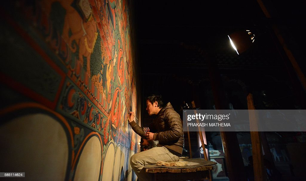 In this photograph taken on June 15, 2016, a Nepalese artist restores sacred murals in a monastry in Lo Manthang in Upper Mustang. Deep in the heart of a medieval monastery in Nepal's remote Upper Mustang region, the battle to restore sacred murals and preserve traditional Tibetan Buddhist culture is in full swing. / AFP / PRAKASH MATHEMA / To go with 'Nepal-Tibet-Buddhism-Architecture-Painting' FEATURE by Ammu Kannampilly