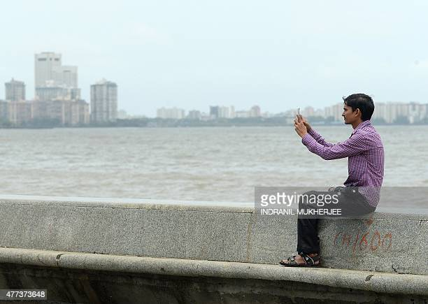 In this photograph taken on June 15 an Indian man takes a 'selfie' on Marine Drive promenade in Mumbai Selfies have become a global phenomenon with...