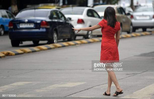 In this photograph taken on June 15 an Indian woman hails a cab at a business district in Mumbai India published new guidelines for webbased...