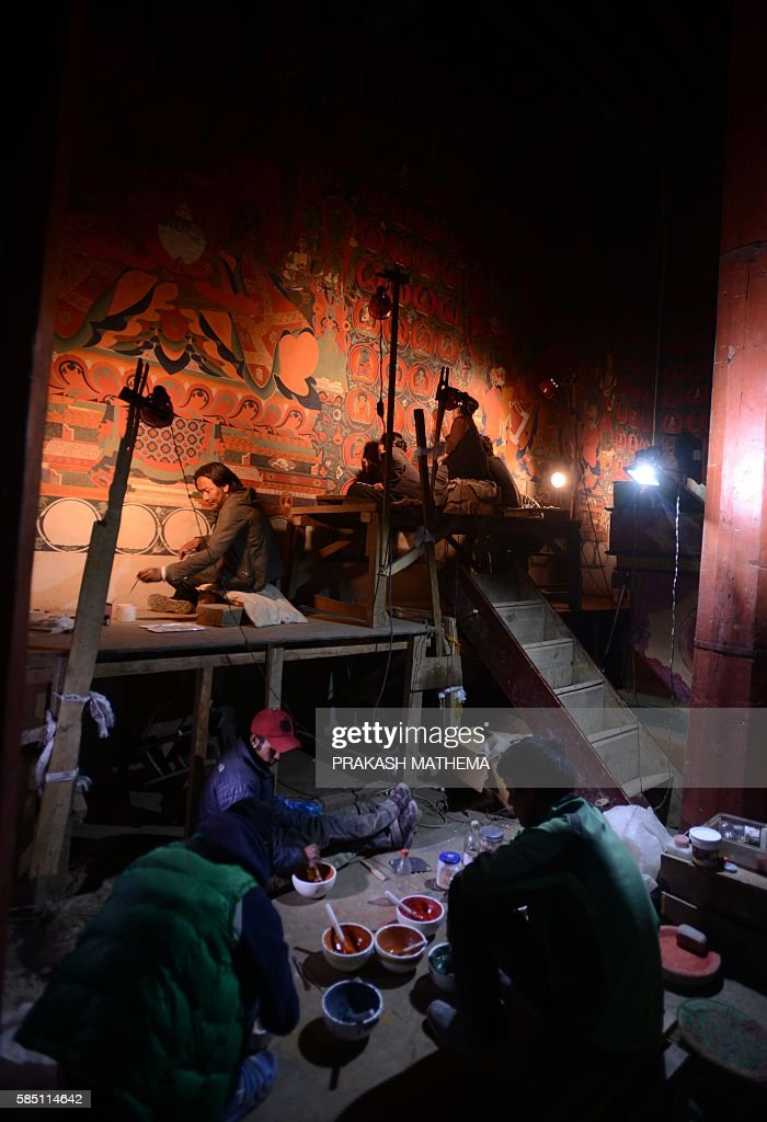 In this photograph taken on June 15, 2016, Nepalese artists restore sacred murals in a monastry in Lo Manthang in Upper Mustang. Deep in the heart of a medieval monastery in Nepal's remote Upper Mustang region, the battle to restore sacred murals and preserve traditional Tibetan Buddhist culture is in full swing. / AFP / PRAKASH MATHEMA / To go with 'Nepal-Tibet-Buddhism-Architecture-Painting' FEATURE by Ammu Kannampilly