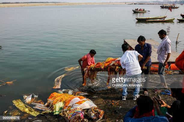 In this photograph taken on June 2 2018 Indian men dip a dead body into the river Ganges prior to the cremation at the Manikarnika Ghat in the old...