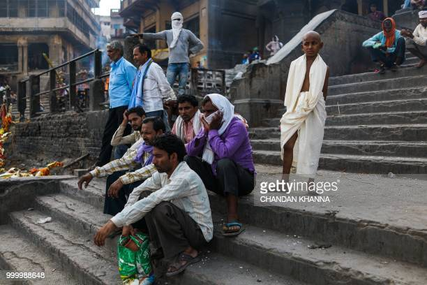 In this photograph taken on June 2, 2018 Indian men wait for a dead body to finish being cremated at the Manikarnika Ghat in the old quarters of...
