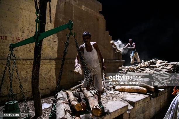 In this photograph taken on June 2, 2018 members of the Dom community use a scale to weigh wood that is used for cremations at the Manikarnika Ghat...