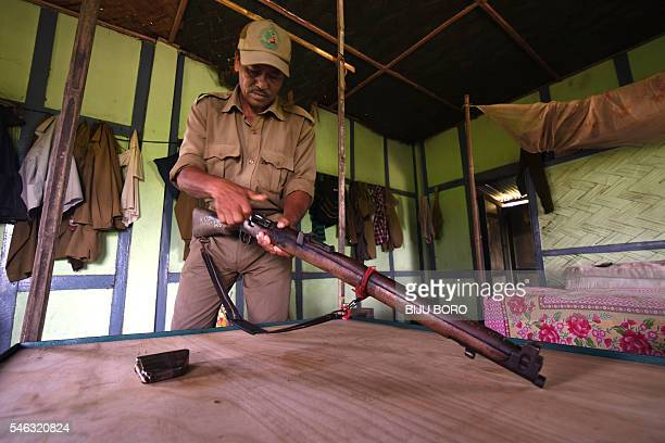 In this photograph taken on June 2 Indian forest ranger Mukeshwar Barpatra checks his rifle in a forestry department building in Kaziranga National...