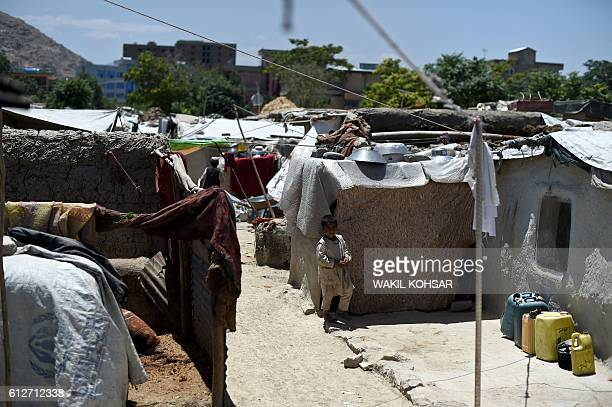 In this photograph taken on June 20 an internally displaced Afghan child walks beside a mudwalled home at a refugee camp in Kabul Pakistan hosts 14...