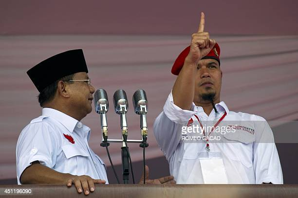 In this photograph taken on June 22 Indonesian presidential candidate Prabowo Subianto looks at rock star Ahmad Dhani who joined him on stage during...