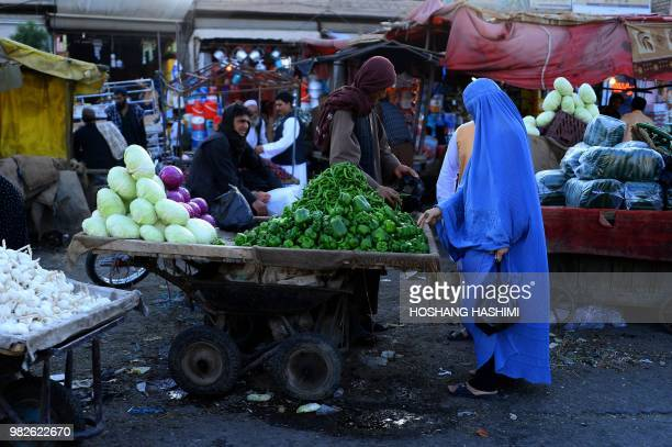 In this photograph taken on June 23 an Afghan burqaclad woman buys vegetables at a market in Herat