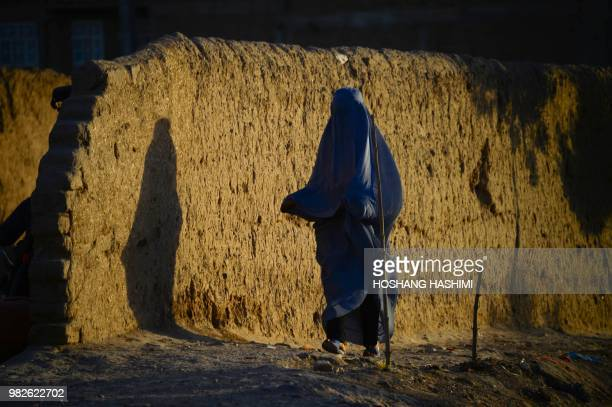 TOPSHOT In this photograph taken on June 23 an Afghan burqaclad woman walks along a road on the outskirts of Herat