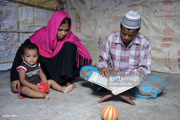 In this photograph taken on June 24 Rohingya Muslim man Mohammed Anwar with his wife read the Koran during the holy month of Ramadan inside their...