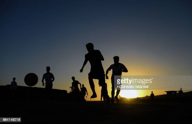 TOPSHOT In this photograph taken on June 25 Afghan youths play football on a field in Herat