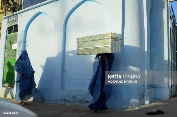 TOPSHOT In this photograph taken on June 26 a Afghan burqaclad woman carries a box on her head along a road in Herat