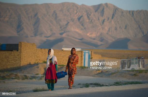 In this photograph taken on June 26 Afghan girls carry a gas cannister on the outskirts of MazariSharif