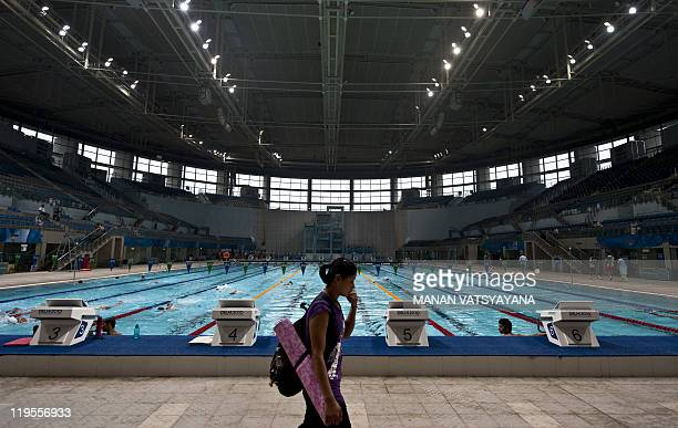 In this photograph taken on June 27 an Indian swimmer arrives to train at The Shayama Prasad Mukherjee Swimming complex, the mains swimming events...