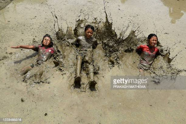 In this photograph taken on June 29 2020 children play in a rice paddy field during National Paddy Day which marks the start of the annual rice...