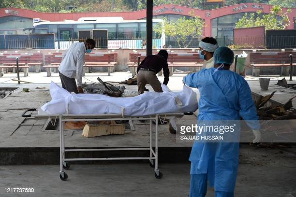 In this photograph taken on June 3, 2020 workers and relatives wearing Personal Protective Equipment prepare the cremation pyre for a person who died...
