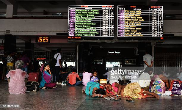 In this photograph taken on June 30 Indian passengers take a nap inside New Delhi railway station in New Delhi India's new government is rolling out...