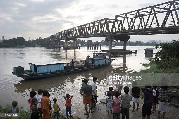 In this photograph taken on June 4 2012 a crowd of Indonesian residents send off a wooden boat transporting a toothless crocodile named Hollande...