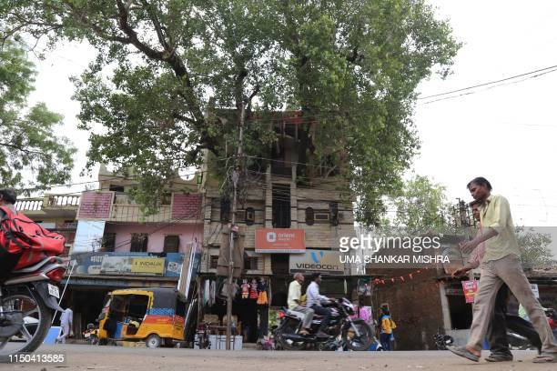 In this photograph taken on June 4 Indian residents walk along a road past the house of the Kesharwani family, which was built around a peepal tree ,...