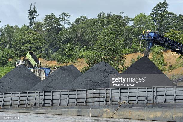 In this photograph taken on June 5 2012 coal are loaded in a barge for transport on a river in Central Kalimantan province on Indonesia's Borneo...