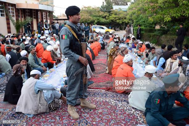 In this photograph taken on June 5 an Afghan policeman stands guard as others wait to break their fast during the Islamic holy month of Ramadan at a...