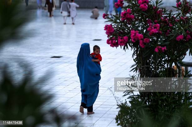 In this photograph taken on June 6 an Afghan burqaclad woman holds a child as she walks in the courtyard of the Hazrate Ali shrine also called 'Blue...